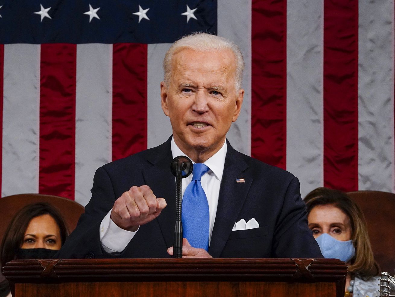 President Joe Biden standing and speaking with an American flag behind him and Kamala Harris and Nancy Pelosi in the background.