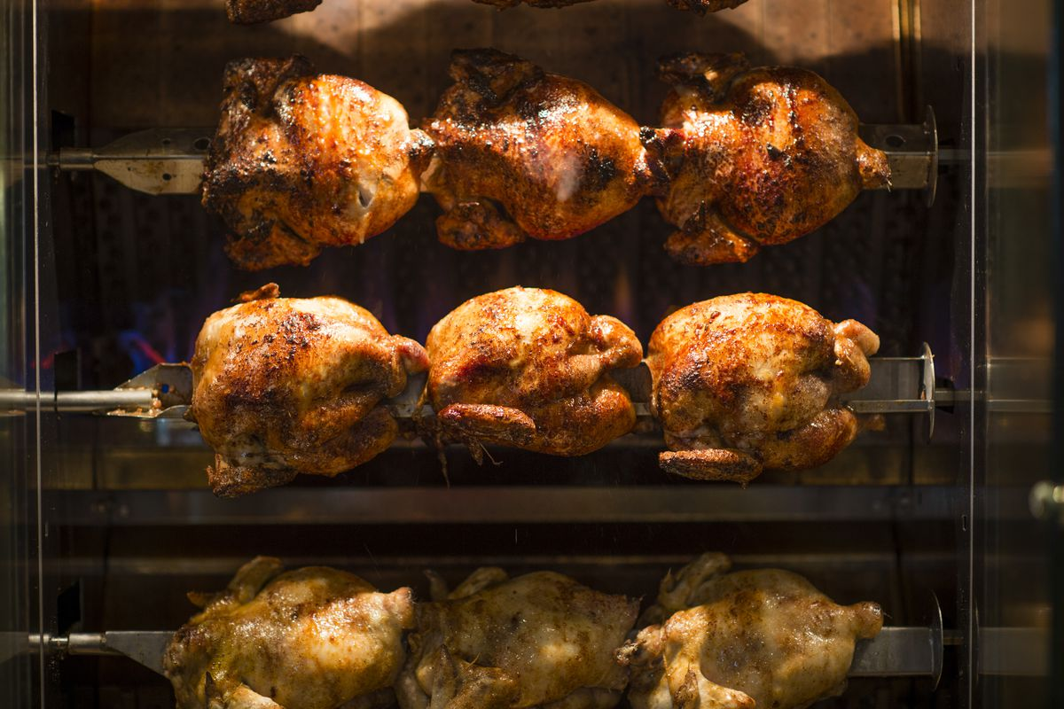 A close-up photo of nine rotisserie chickens roasting at Chicken on the Hill