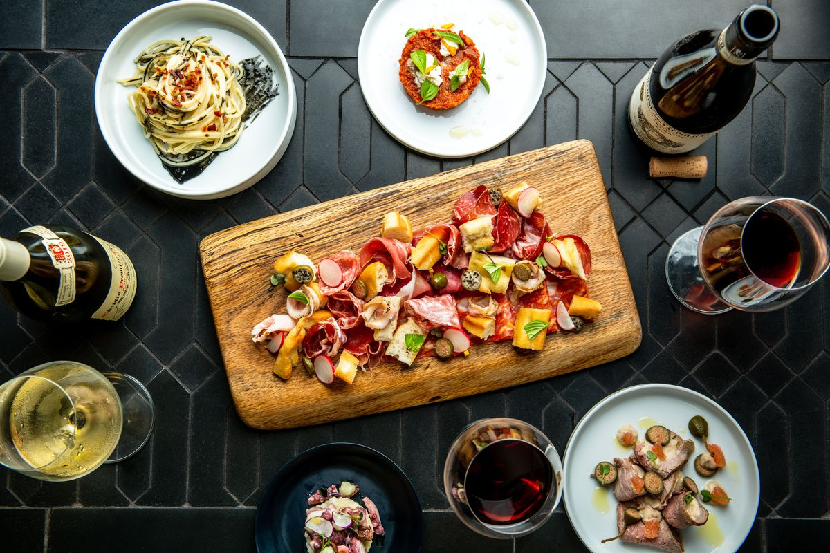 an overhead spread of italian dishes including charcuterie, pasta and several glasses of wine