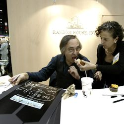 """Artist and author Art Spiegelman gets some help with his lunch from Francoise Mouly, of Random House, during a signing of Spiegelman's new book """"In the Shadow of No Towers"""" at the Book Expo America convention, Saturday, June 5, 2004, in Chicago."""