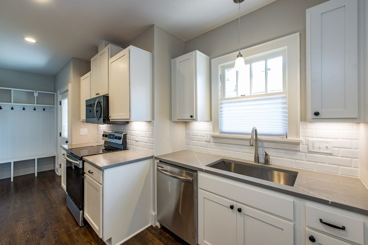 White kitchen with white cabinets, stainless appliances and dark hardwood floors.