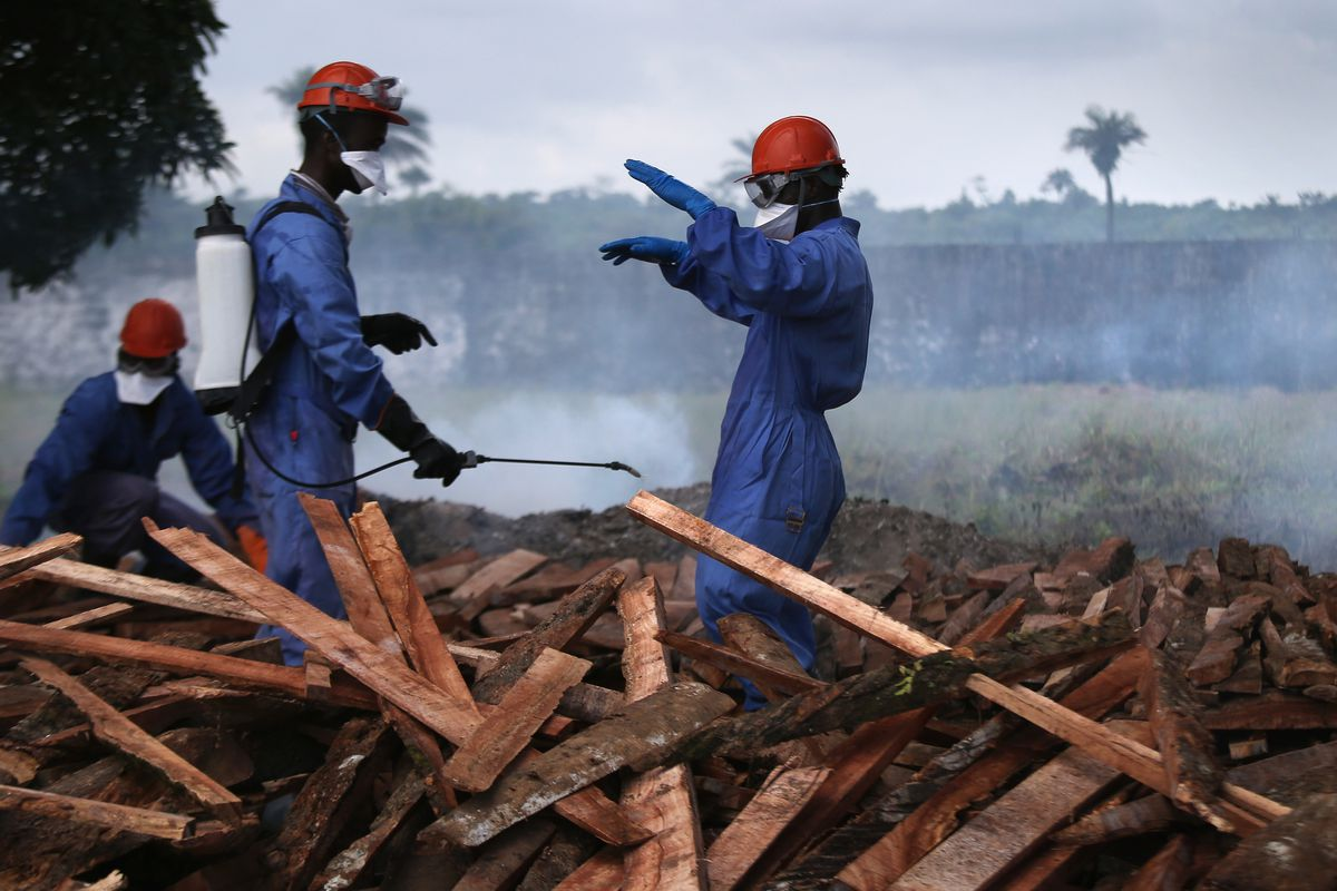 Burial teams from the Liberian Ministry of Health disinfect themselves before burning the bodies of Ebola victims in Marshall, Liberia.