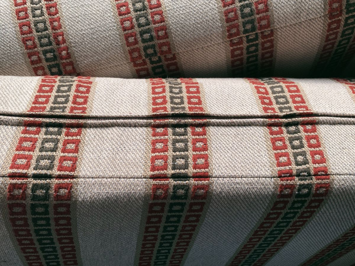 A closeup of sofa cushion's fabric that is in a tan, red, and green striped pattern. There is a visible seam for the zipper.