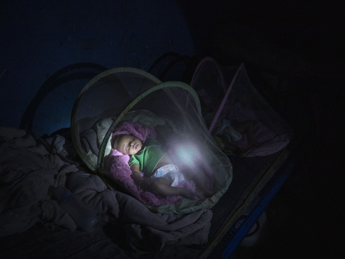 Tigrayan refugee Abraha Kinfe Gebremariam, 40, uses a flashlight to check on his 4-month-old twin daughters Aden and Turfu after praying at a church early in the morning in Hamdayet in eastern Sudan, near the border with Ethiopia. Even as Tigrayans ran for their lives or jostled for space on a boat to safety, the sight of the tall, silent, sorrowful man carrying the tiny twin girls made people pause.