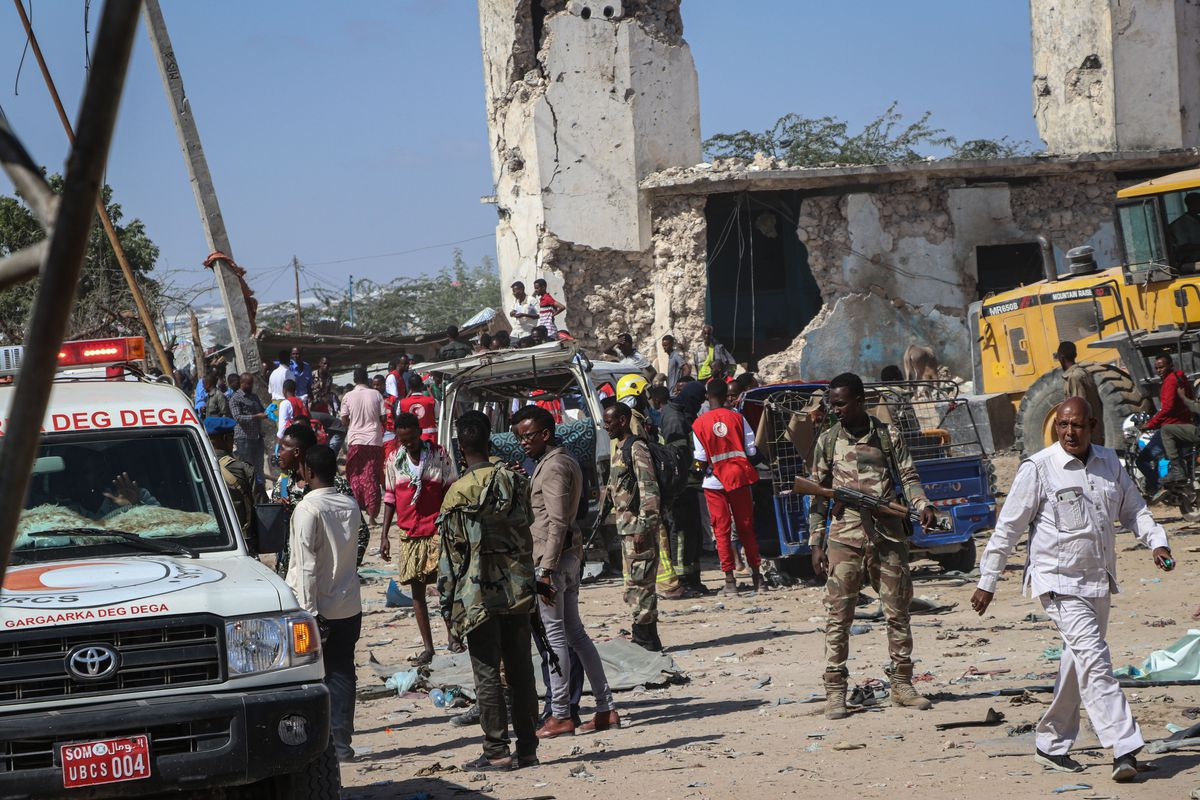 Soldiers and emergency vehicles in the site of the blast; damaged vehicles and buildings can be seen in the background.