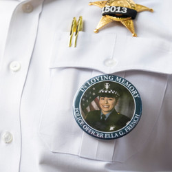 An officer wears a pin in memory of Officer Ella French at a prayer service for her Wednesday.