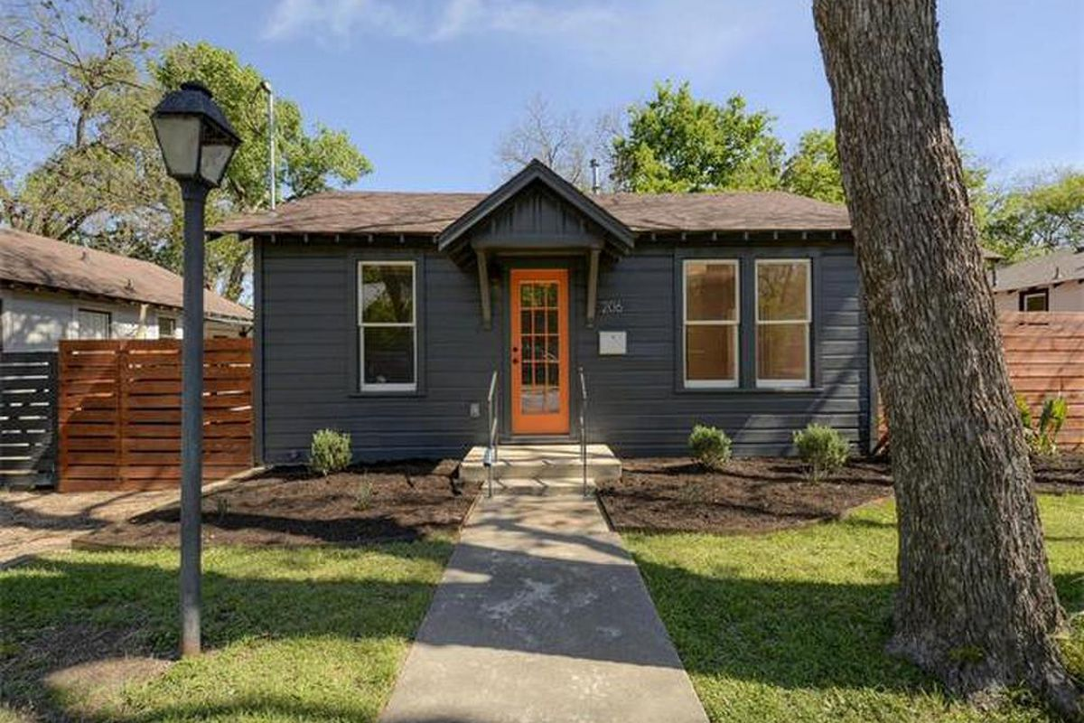Small wooden cottage painted dark gray with bright orange door