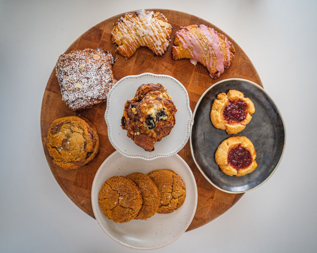 A wooden tray with several pastries on it