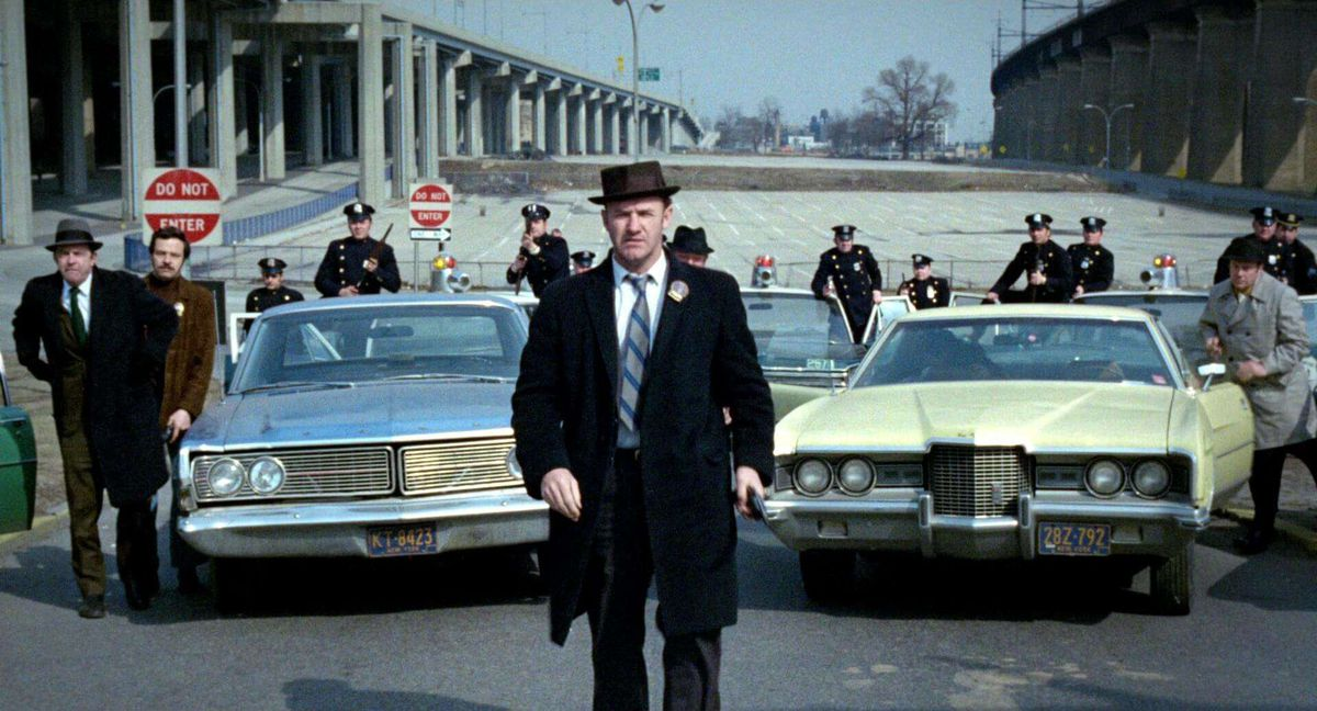 Gene Hackman stands in front of a row of police.