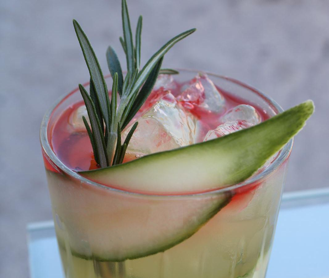 A pink cocktail is in a low glass filled with long cucumber slices and a rosemary sprig