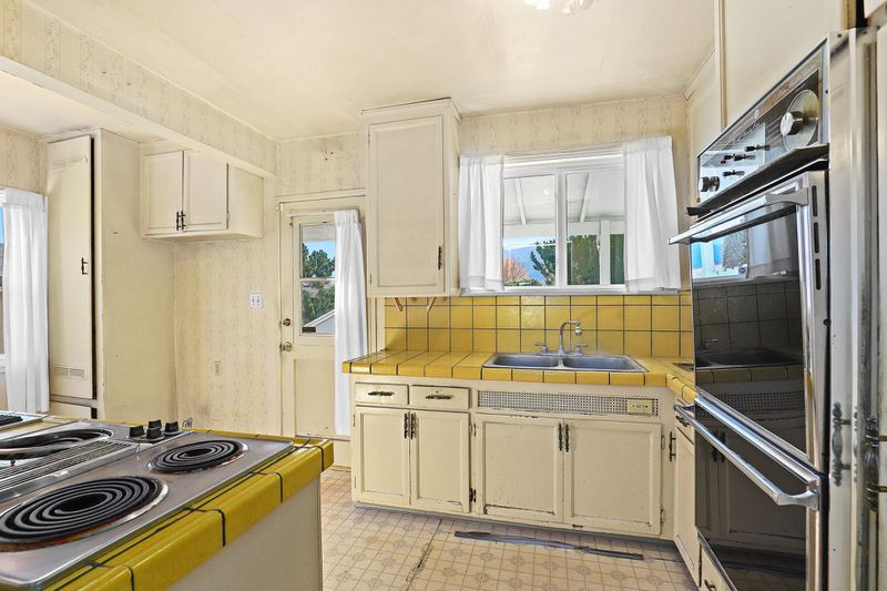 A roomy kitchen with yellow tile and older appliances.