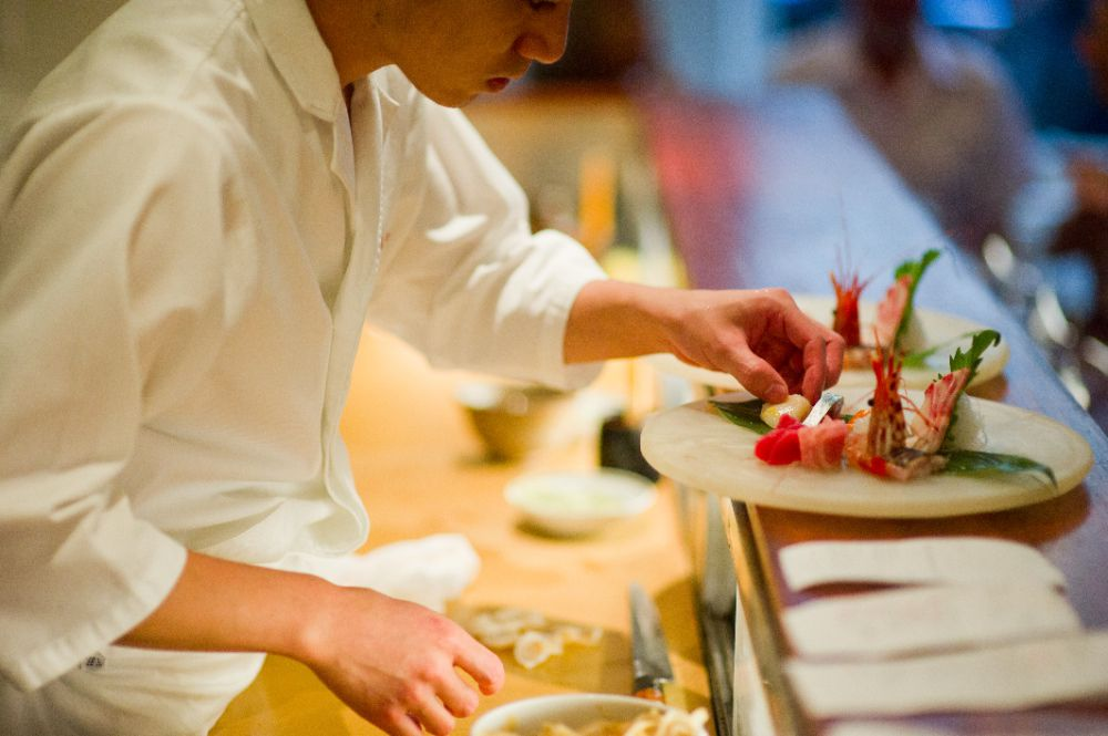 A sushi chef leans over a counter placing items on a plate of sashimi