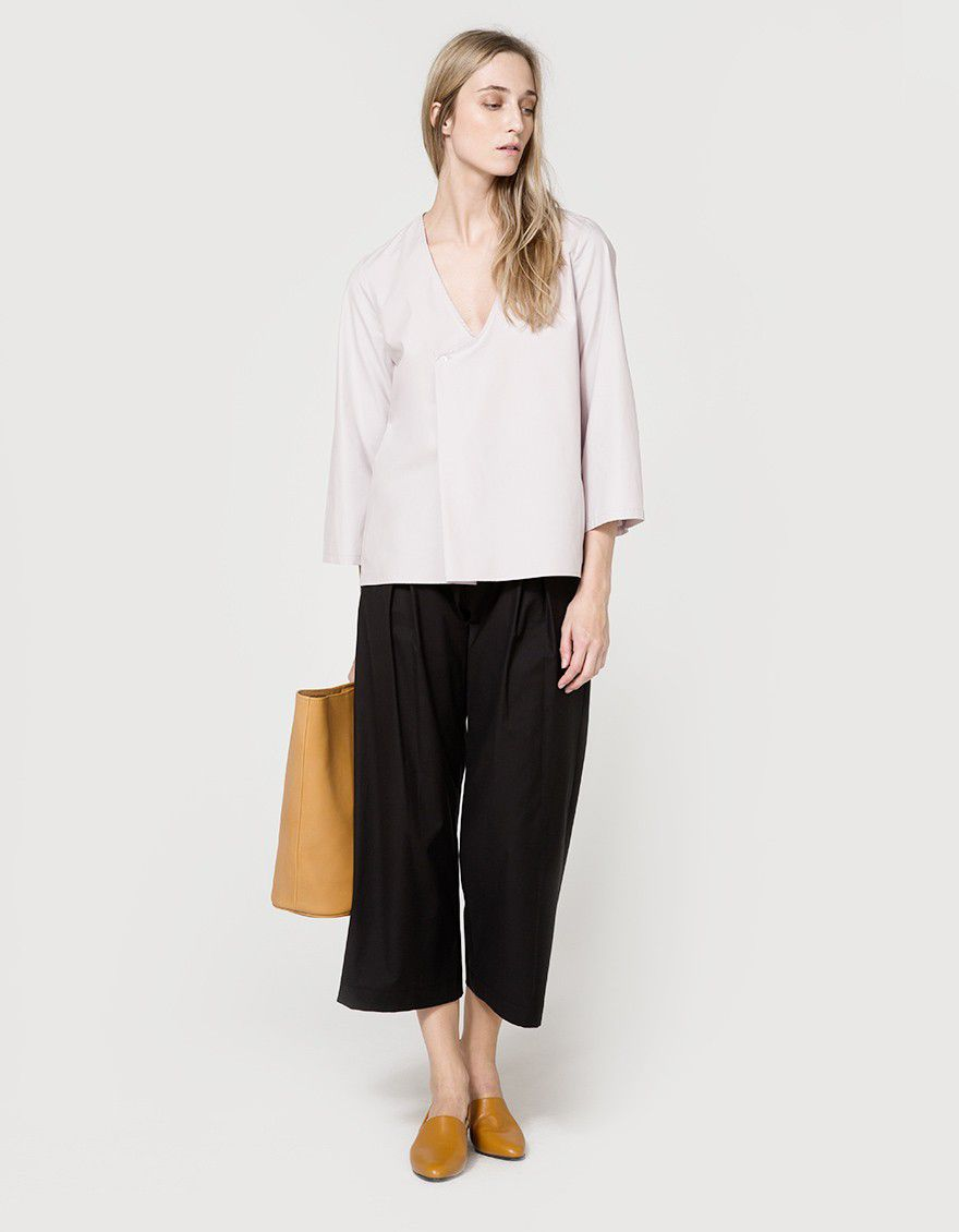 ed24b697b58e8 Woman in mauve colored blouse, black culottes and tan slip on shoes