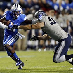 Jamaal Williams (21) of the Brigham Young University Cougars runs the ball against B.J. Larsen (99) of the Utah State Aggies during NCAA football in Provo, Friday, Oct. 3, 2014.