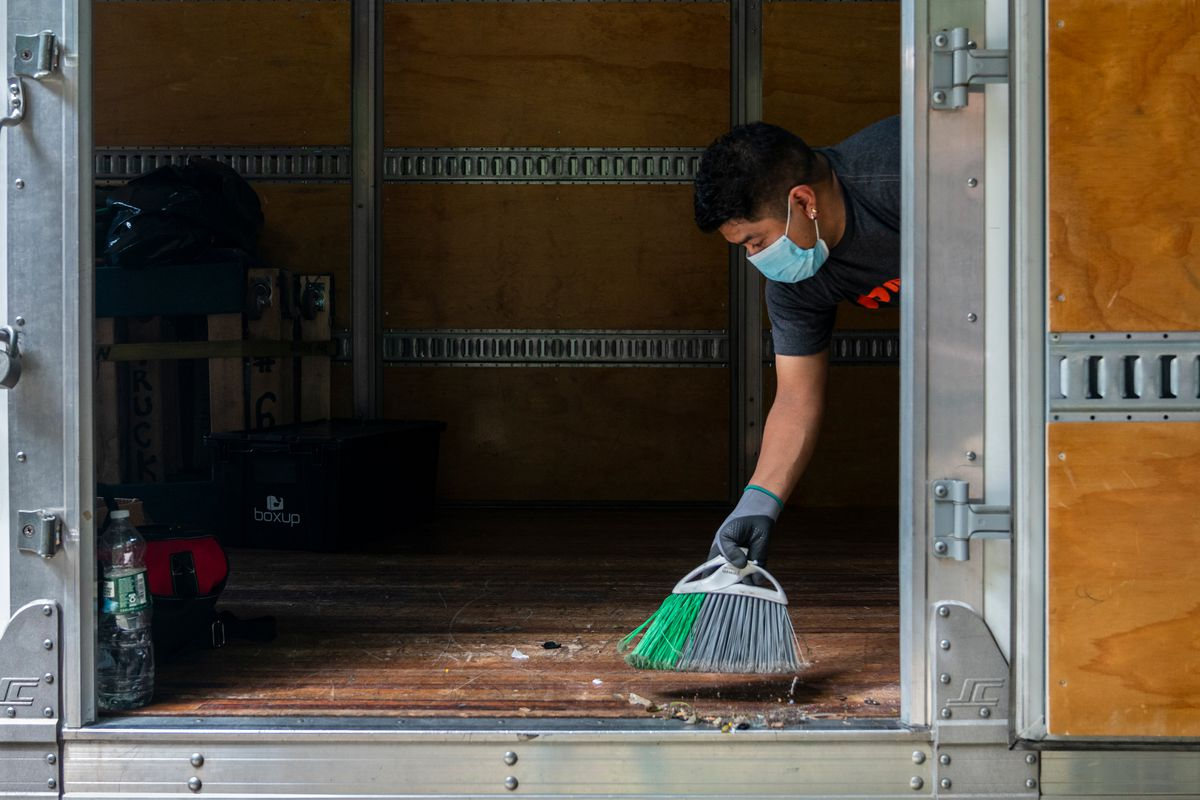 Alfredo Plaza sweeps dirt off the moving truck just before heading back to the storage facility in Gowanus, Aug. 14, 2020.
