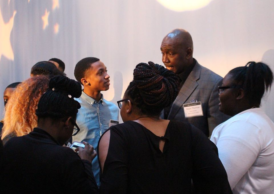 """Teens at """"The Black Table,"""" a Black History Month event sponsored by BUILD, Inc., gather around retired basketball player Deon Thomas of the Big Ten Network, who was the all-time leading scorer in Fighting Illini history, and spent his 14-year professiona"""
