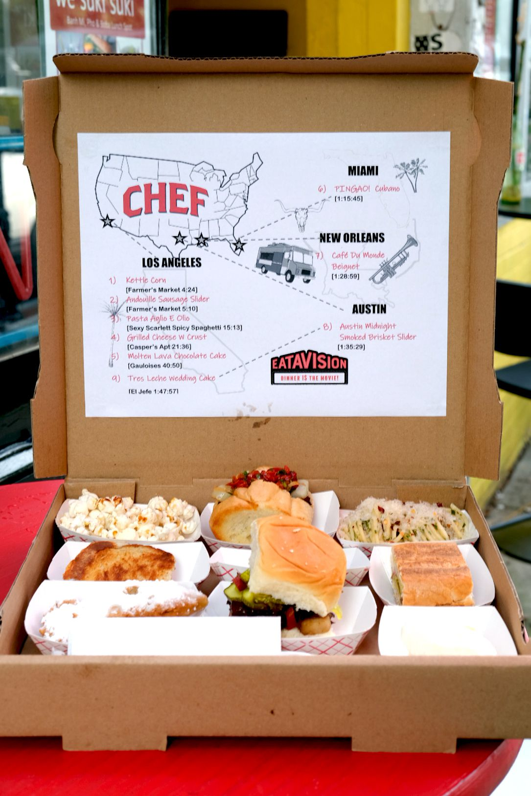 """A takeout pizza box filled with sandwiches, popcorn, pasta, dessert for the tasting menu and movie screen of """"Chef"""" by Eatavision"""