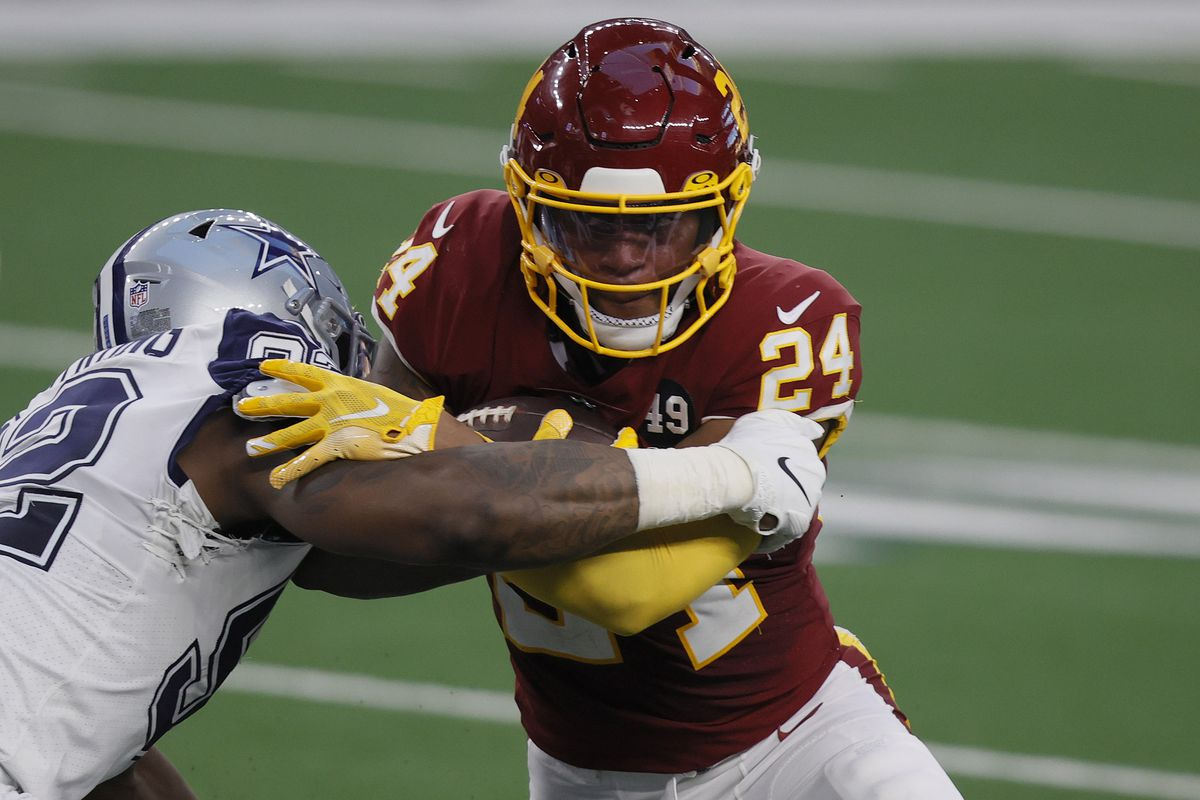 Antonio Gibson #24 of the Washington Football Team carries the ball against Dorance Armstrong #92 of the Dallas Cowboys in the first half at AT&T Stadium on November 26, 2020 in Arlington, Texas.