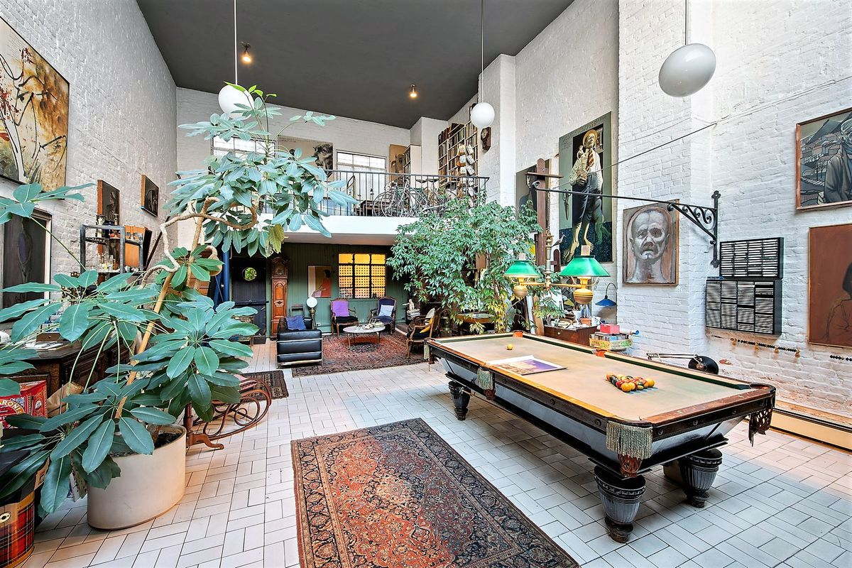 A open living area with 20-foot ceilings, a pool table, and a large skylight.