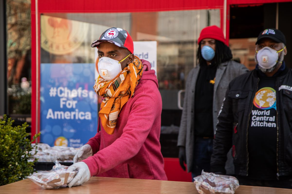 The chef Marcus Samuelsson wears a mask as he serves food in front of his Harlem restaurant the Red Rooster