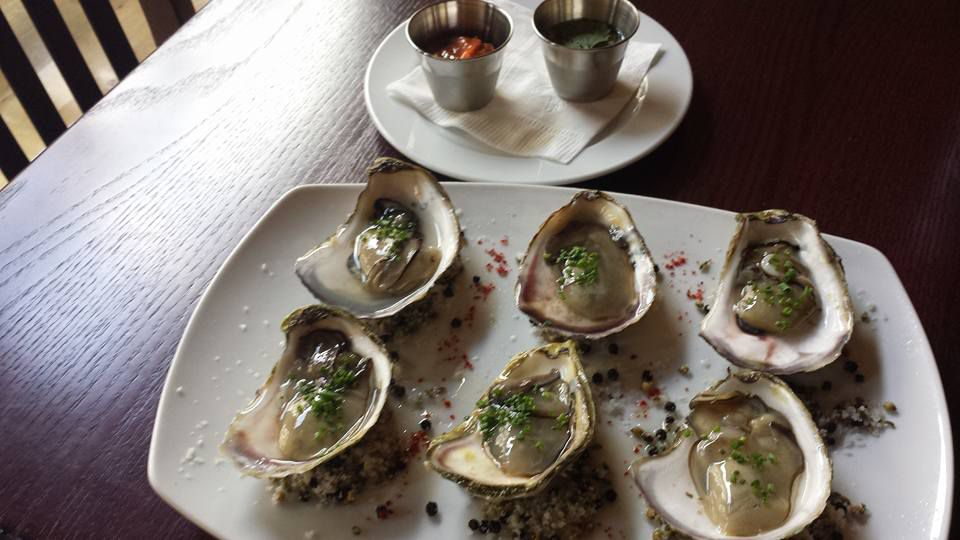 A white plate of six oysters on a dark wooden table