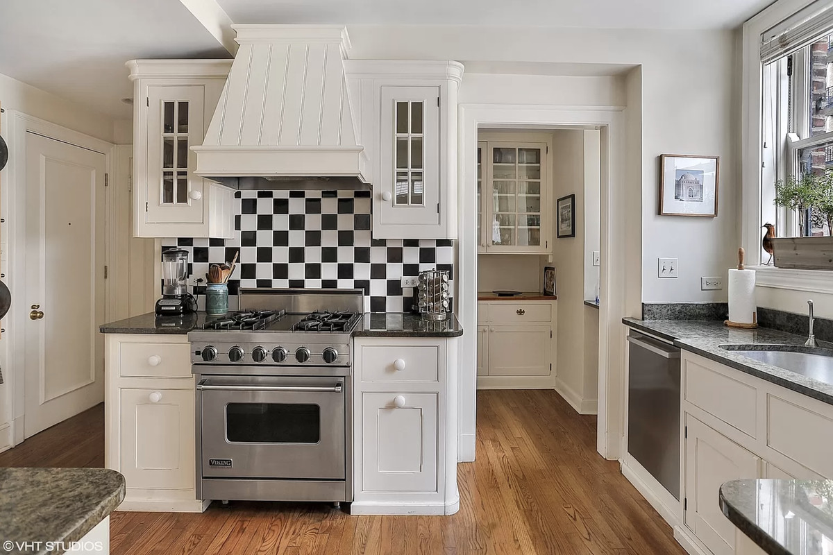 A kitchen with white cabinets, a checkered tile backsplash, a butler's pantry, and a window over the sink.