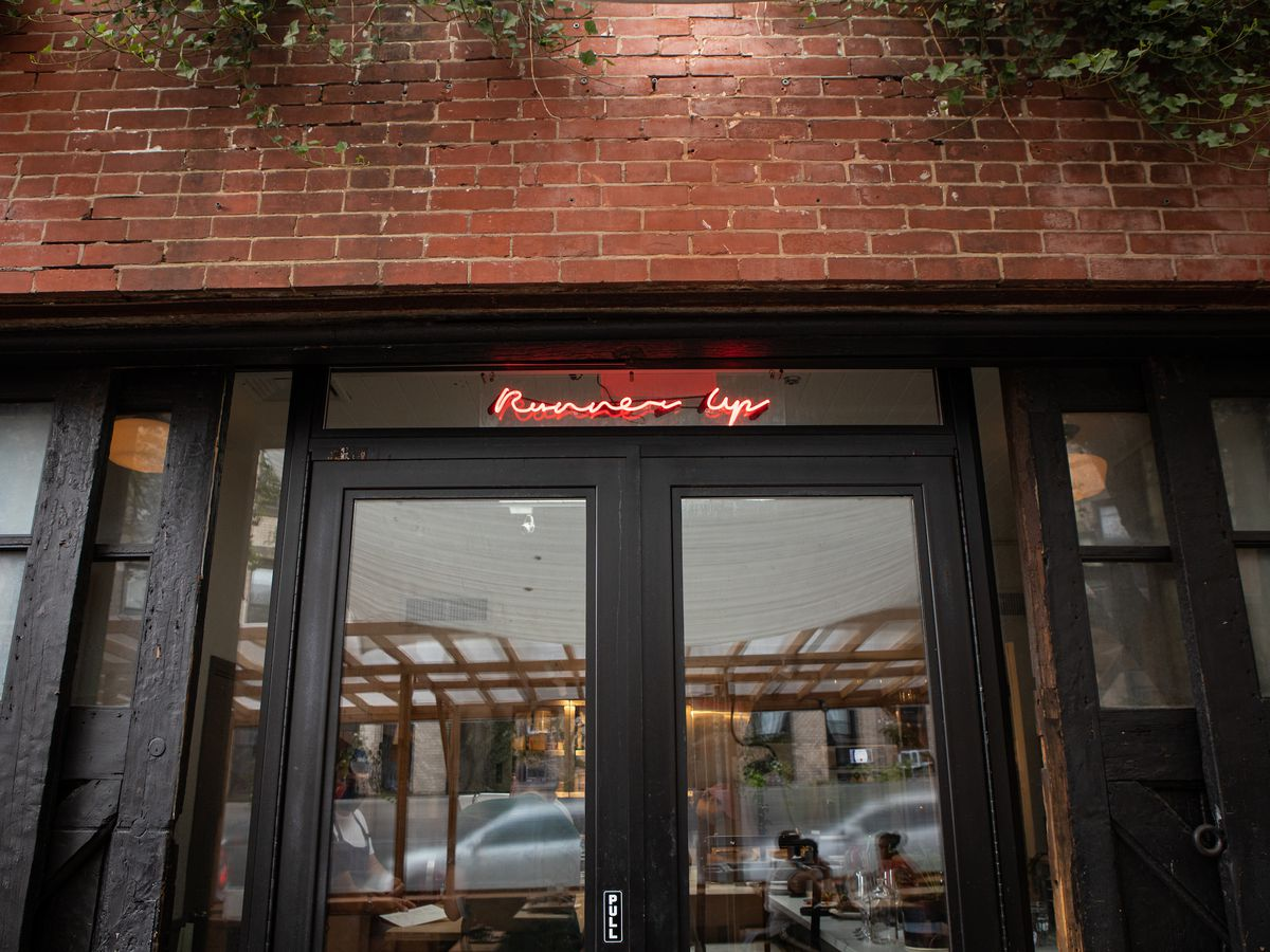"""A brick storefront with glass windows and a neon sign with cursive lettering that reads """"Runner Up"""""""