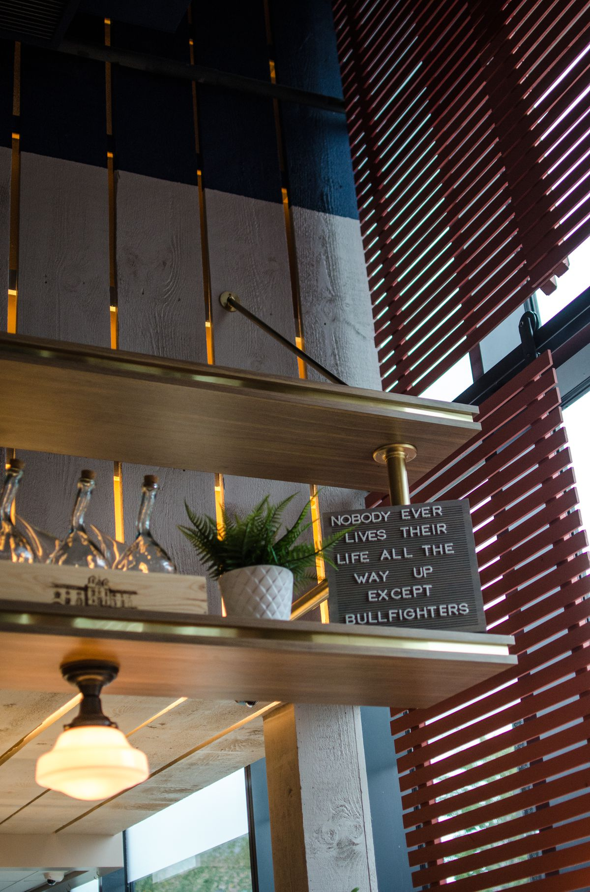 """Closeup on decor on a high shelf inside a restaurant, including a set of three porróns and a sign that says """"nobody ever lives their life all the way up except bullfighters"""""""