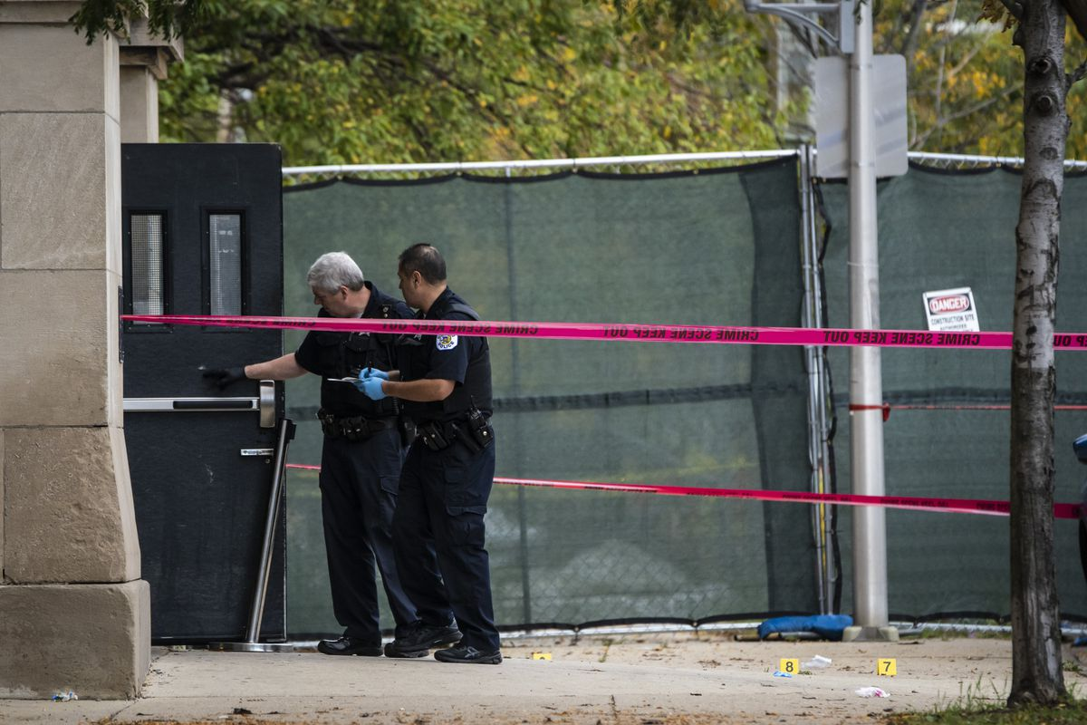 Evidence technicians note a mark on a door where it was struck by a bullet after a 14-year-old girl and a security guard were both shot Tuesday afternoon outside Wendell Phillips Academy High School in the 3800 block of South Giles in Bronzeville.