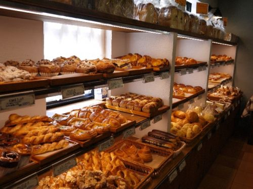 Shelves of pastries and bread loaves in front of a window