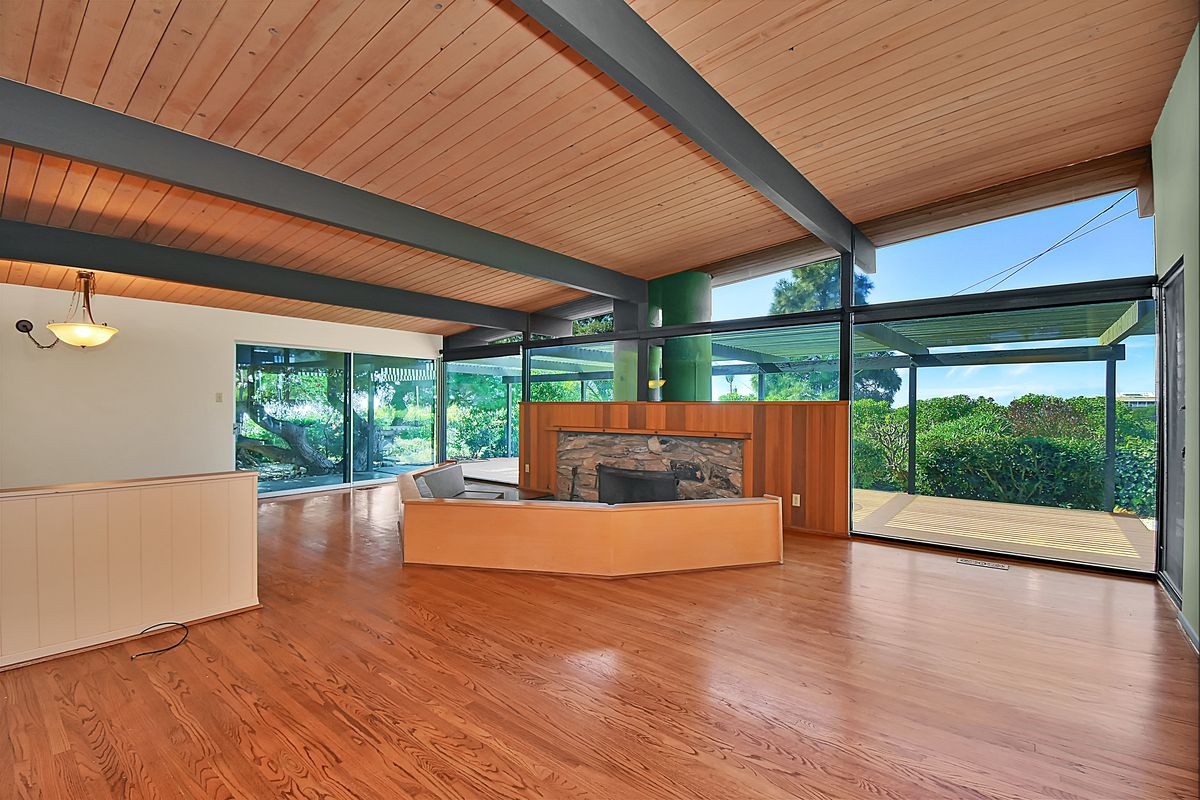 A room with wood floors and enormous windows on the far wall, where there's also a fireplace