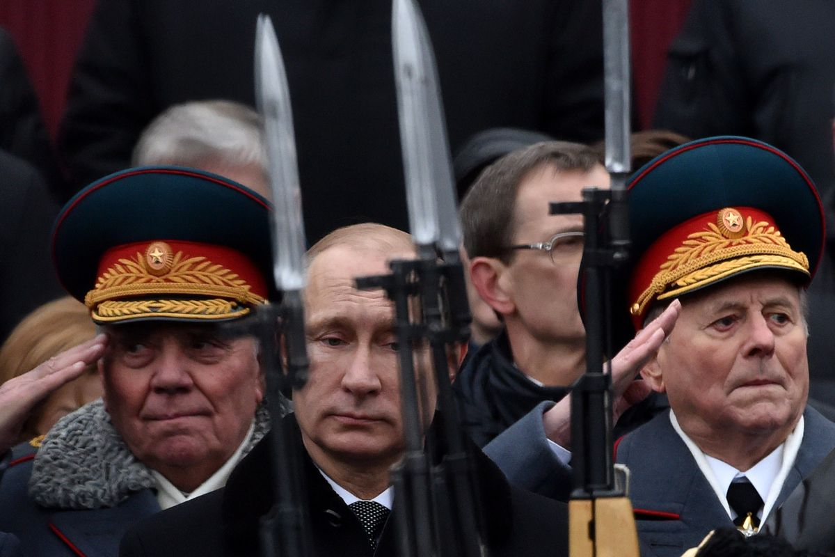 Russian President Vladimir Putin (C) reacts after a wreath laying ceremony at the Tomb of the Unknown Soldier by the Kremlin wall to mark the Defender of the Fatherland Day in Moscow on February 23, 2015.