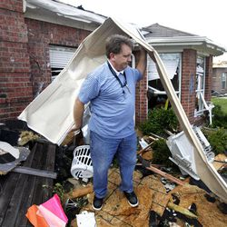 """Randy McKeever, removes part of what he believes is his neighbors garage door from the front of his tornado damaged home Wednesday, April 4, 2012, in Forney, Texas. The mayor of Forney, Texas, says it's """"a real blessing"""" that nobody was killed in the community by the tornadoes that ripped through parts of the Dallas area yesterday."""