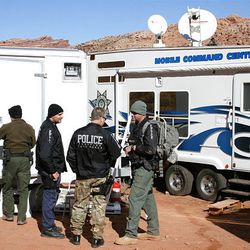 Various law enforcement officers gather near the command center where search efforts are being coordinated.