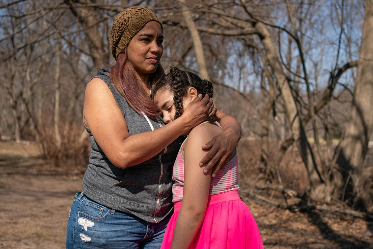 Alexandra Sierra and one of her daughters hug outside their home in Bergen County, New Jersey.