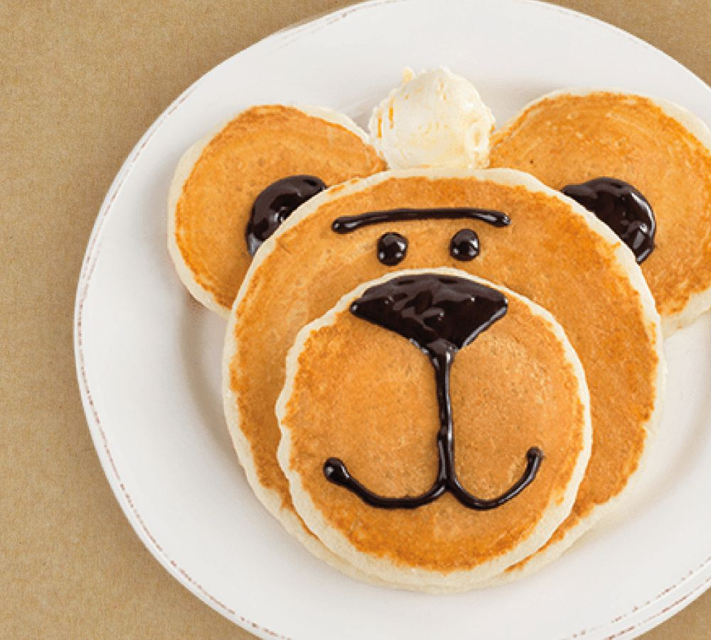 Pancakes of various sizes stacked and decorated with chocolate syrup to resemble a bear's head
