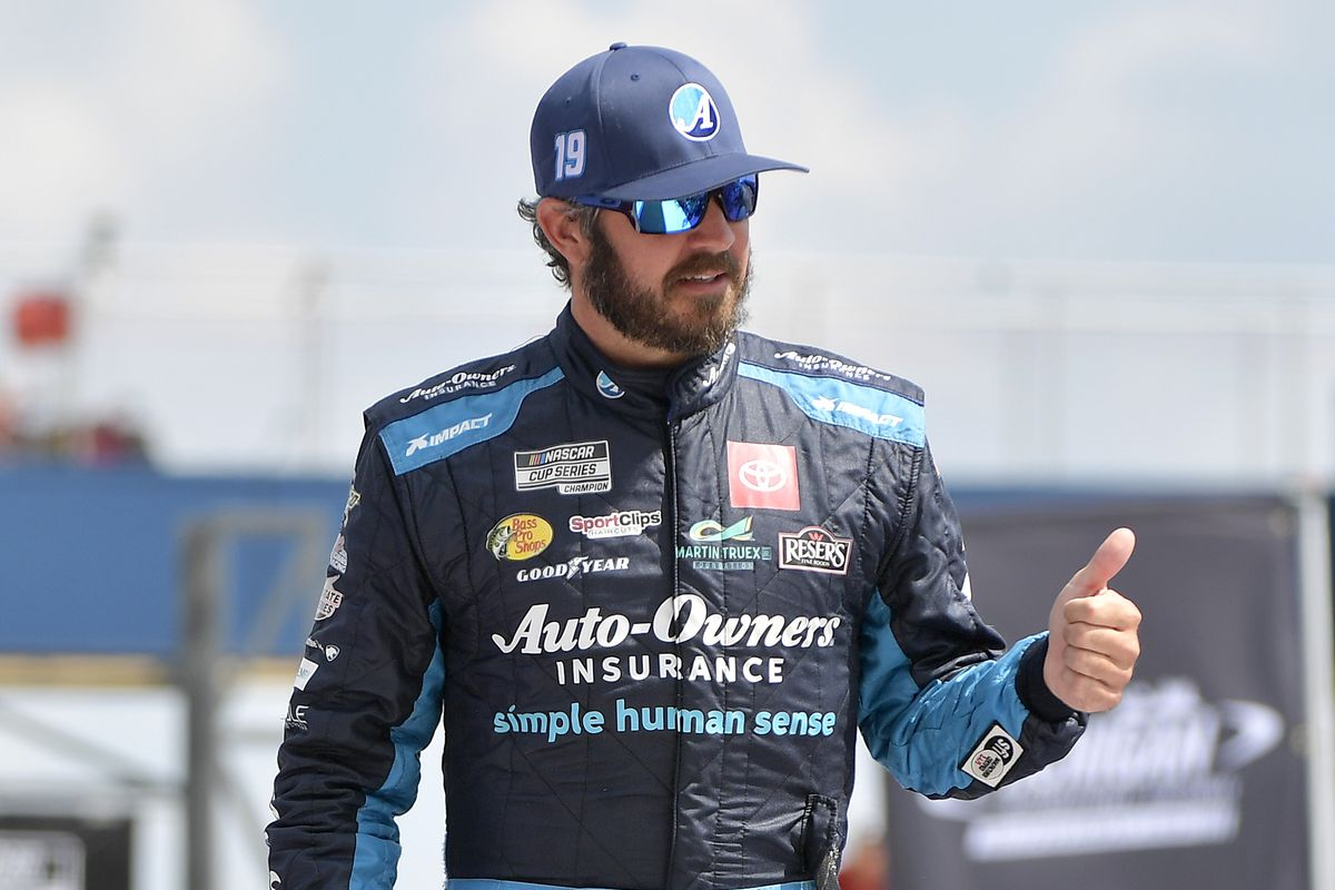 Martin Truex Jr., driver of the #19 Auto-Owners Insurance Toyota, walks on stage during driver introductions prior to the NASCAR Cup Series FireKeepers Casino 400 at Michigan International Speedway on August 22, 2021 in Brooklyn, Michigan.