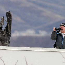 An investigator photographs the wreckage as he examines the remains of a helicopter that crashed onto an empty building yesterday afternoon, killing two men on board, Wednesday, Dec. 3, 2014, in North Salt Lake.