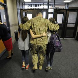 Air Force Tech Sgt. Edward Goettig walks out of Lehi Junior High School with his arms wrapped around his daughters Bailee, left, and Sydney as his wife, Tracie, at left, checks out the office after Edward surprised Sydney at her school with his return home a week earlier than originally planned on Thursday, March 6, 2014. Goettig had been deployed to Afghanistan since Aug. 27, 2013.