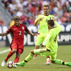 United States defender DeAndre Yedlin (2) kicks the ball past Venezuela's Rupert Quijada (4) and Christian Santos (19) during a soccer game at Rio Tinto Stadium in Sandy on Saturday, June 3, 2017. They tied 1-1.