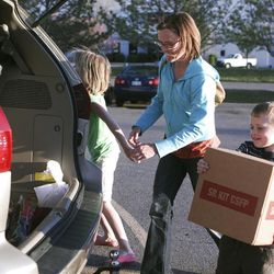 Judy Moore, of Taylorsville, Utah, and her son load a box of food into the back of her van. The family delivers meals to homebound seniors together once a month.