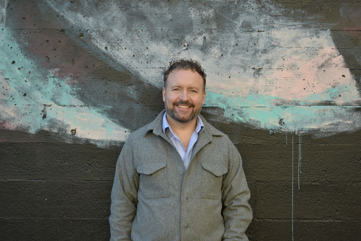 Kurt Huffman, the owner of Chefstable, stands in front of a backdrop with rough splotches of turquoise, pink, and silver. He's a white man with a goatee, wearing a grey coat over a blue button-up