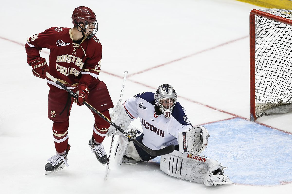 UConn goaltender Rob Nichols watches closely as a puck goes wide of the net with BC forward Zach Sanford applying pressure.