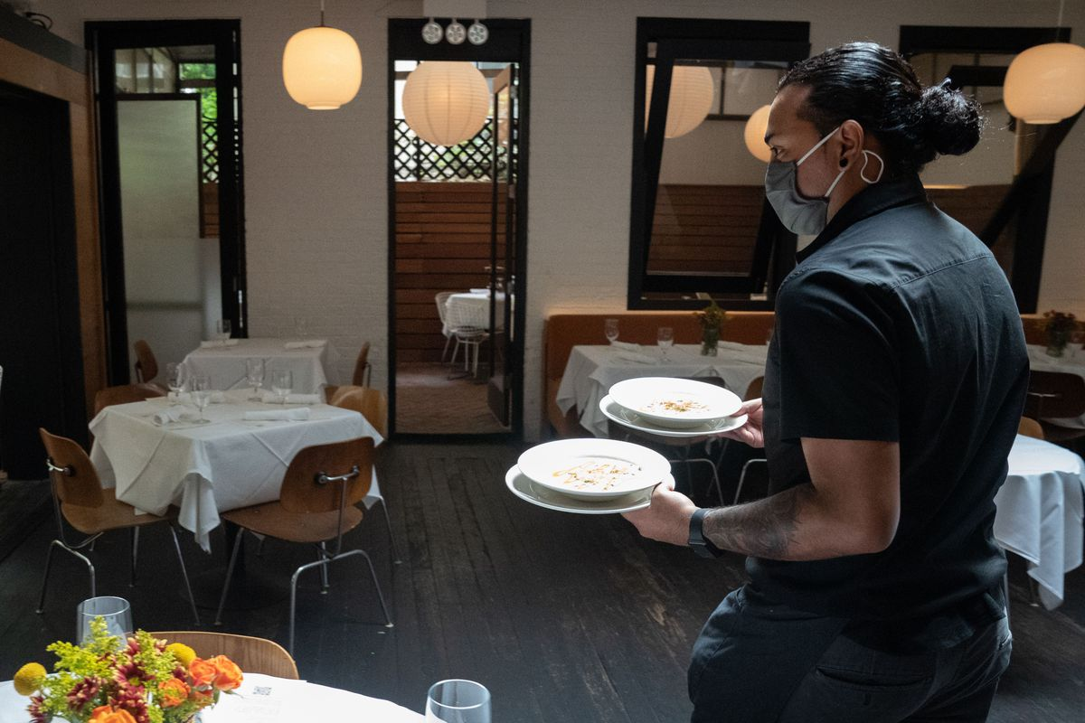 A waiter delivers food to a table at Bottino Restaurant in Chelsea as New York City restaurants open for limited capacity indoor dining on October 1, 2020 in New York.