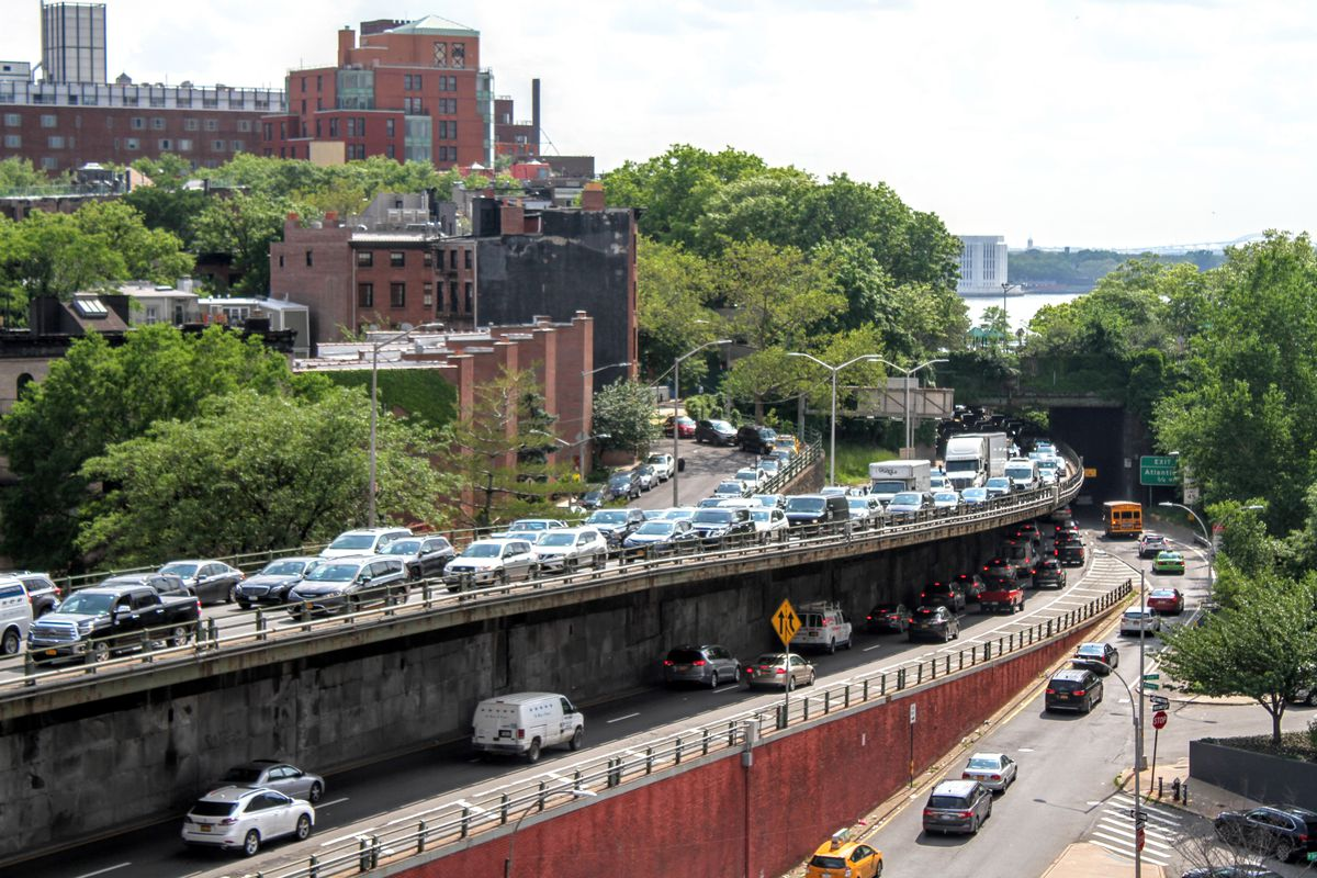 A NYC highway with traffic, buildings on the back.