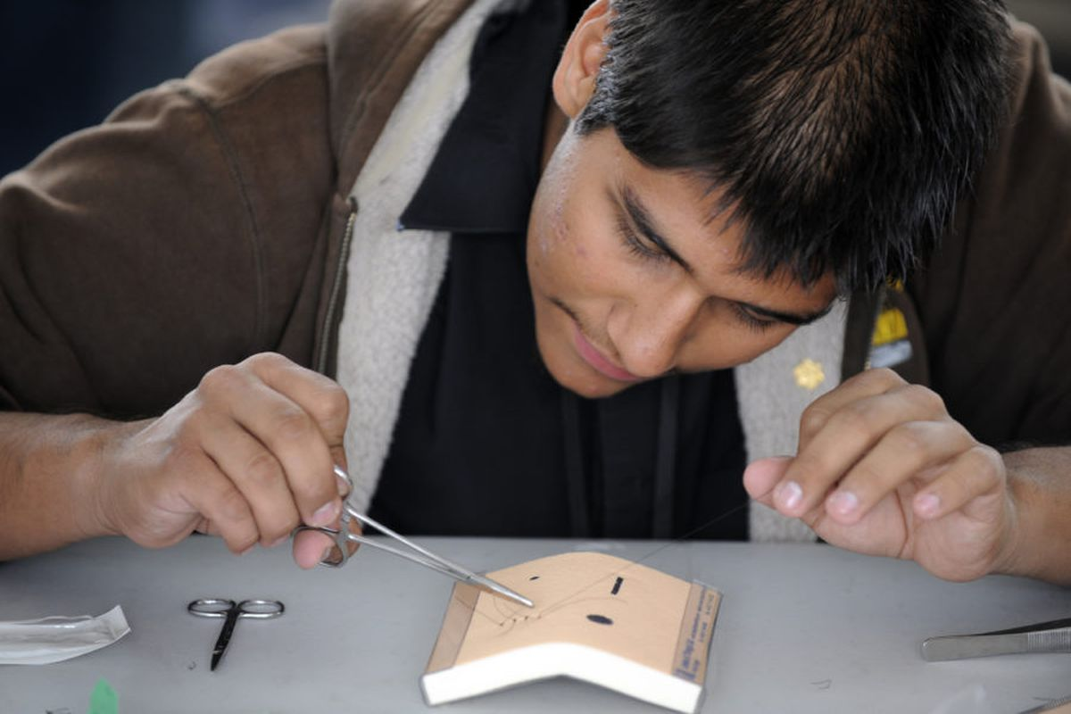 Health care professions are the focus of IDEA's first school attempting the diverse-by-design model. Pictured is a student practicing how to make sutures at a health careers expo in Colorado.