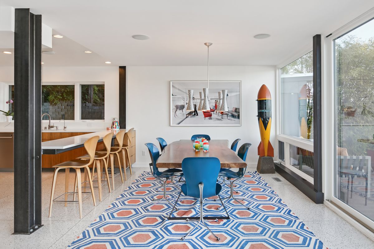 A dining room has a geometric red and blue rug, blue chairs, and a wooden table.