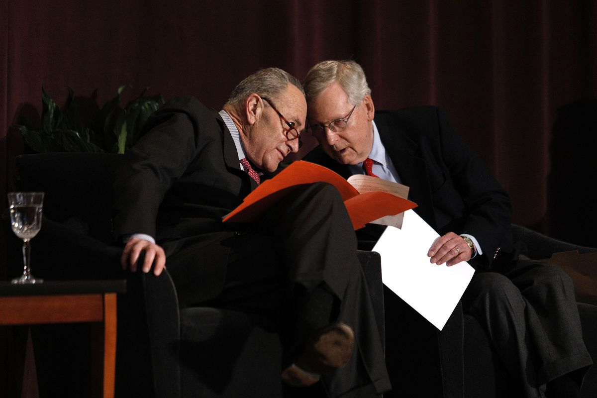 US Senate Majority Leader Mitch McConnell and US Senate Democratic Leader Chuck Schumer sitting beside each other with their heads together in conversation.