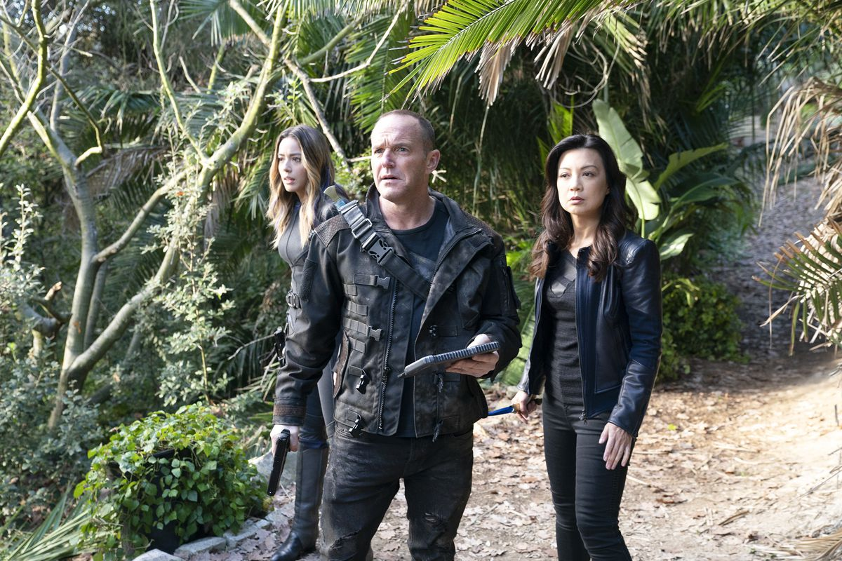 A man and two women stand on a beach in front of a forest. They are all looking vaguely lost and wearing black.