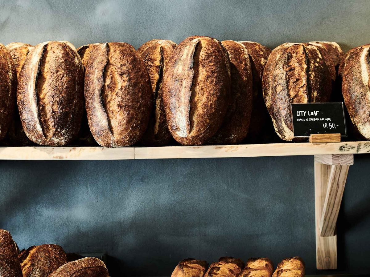 """A wooden shelf holds loaves of sourdough bread rested on end against a slate wall behind, with a small chalkboard sign that reads """"City Loaf"""""""